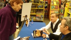 Dave and John signing a copy of the new book for a fan.